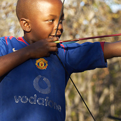 zimbabwean boy playing with a bow and arrow