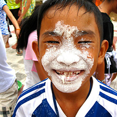 vietnamese boy having fun with cream pie
